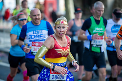 © Licensed to London News Pictures. 03/10/2021. LONDON, UK. A runner in a Wonder Woman costume on Embankment passes mile 25 in the London Marathon, the first time it has been held since April 2019 due to the Covid-19 pandemic.  Over 36,000 elite athletes, club runners and fun runners are taking part in the mass event, with another 40,000 people taking part virtually.  Photo credit: Stephen Chung/LNP