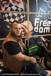 Benzina Alessio Ugolotti in the Holy Freedom display booth with a custom Ironhead Harley-Davidson Sportster during EICMA, the largest international motorcycle exhibition in the world. Milan, Italy. November 21, 2015.  Photography ©2015 Michael Lichter.