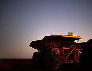 """Iron ore haulage trucks wait at the """"go line"""" for a shift to start at a mine site in the Pilbara region of Western Australia."""