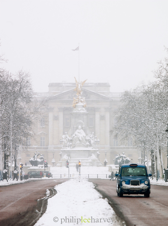 A London Black taxi cab driving down the Mall, away from Buckingham Palace, covered in snow in London, UK