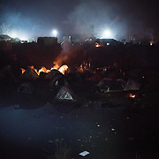 Tents in a flooded trench between the border and the transit camp of Idomeni, Greece. People light fires to warm up, sometimes burning plastic. <br /> <br /> Thousands of refugees are stranded in Idomeni unable to cross the border. The facilities are stretched to the limit and the conditions are appalling.