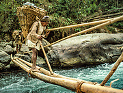 Porters carry doko baskets of trekking gear across bamboo bridge, side stream to main Arun Valley, Nepal