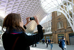 © licensed to London News Pictures. London, UK 19/03/2012. A woman taking a picture on her mobile phone of the new concourse at King's Cross train station in London which opened to commuters today (19/03/2012). Photo credit: Tolga Akmen/LNP