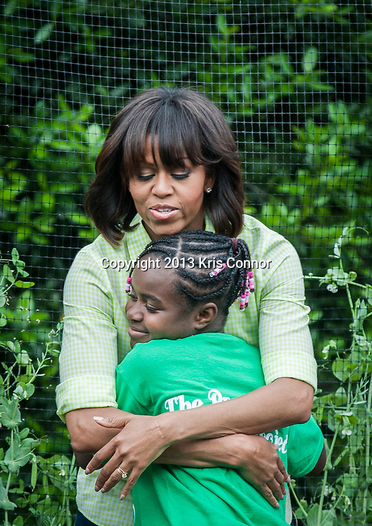 Eliza Croom of Sarah Moore Greene Magnet Technology Academy School, Knox County, TN  hugs the First Lady Michelle Obama during an event where they and with fellow students harvested the White House Kitchen Garden for the fifth year in a row at the White House on May 28, 2013 in Washington DC. Photo by Kris Connor