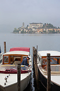 Boat captain on his boat with Isola San Giulio on Lake Orta, Piedmont, Italy. For editorial use only.