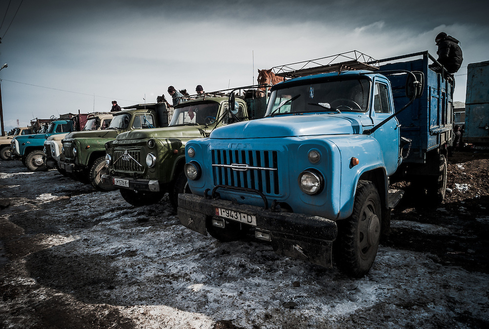 Trucks line up to haul away the bought and unsold horses alike at the end of the weekly animal market in Karakol, Kyrgyzstan.
