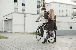 Rear view of a young couple riding a cycle on street, Munich, Bavaria, Germany