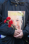 Moscow, Russia, 24/04/2007..The body of former Russian President Boris Yeltsin lies in state in the Cathedral of Christ the Saviour as mourners visit to pay their last respects. A mourner carries flowers and an old magazine with Yeltsin's face on the cover.
