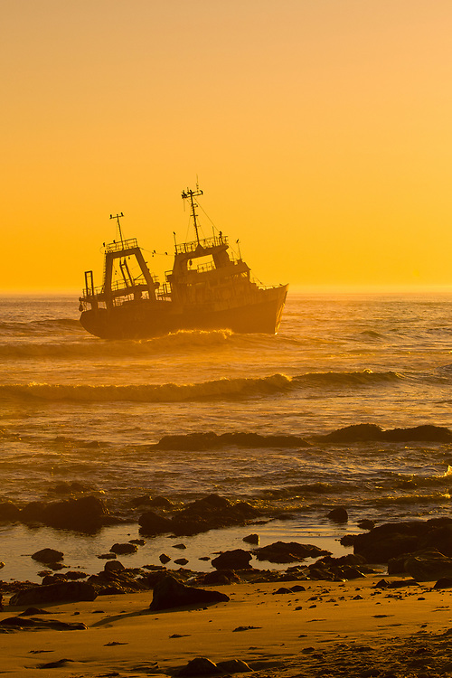 A shipwreck on  the Skeleton Coast at sunset (the Kilmanskop), Swakopmund, (the Atlantic Ocean off of the Namib Desert coastline), Namibia