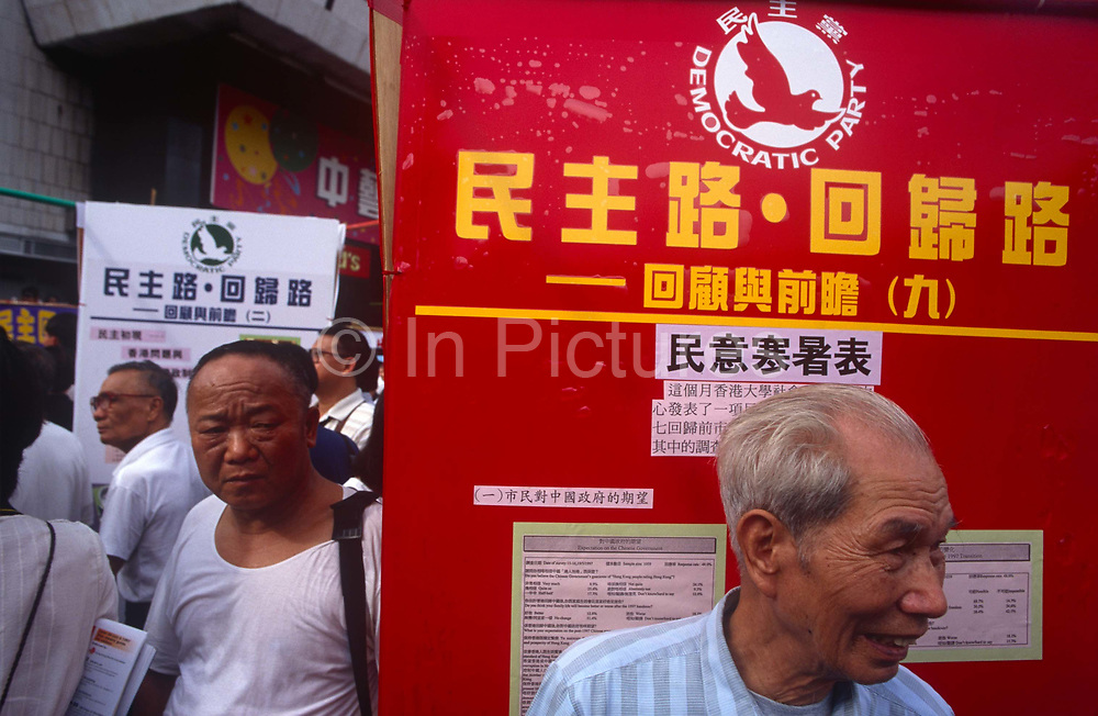 Chinese activist gentlemen and a sign for the Democratic Party of Hong Kong the day after the Handover of sovereignty from Britain to China, on 30th June 1997, in Hong Kong, China. Midnight signified the end of British rule, and the transfer of legal and financial authority back to China. Hong Kong was once known as fragrant harbour or Heung Keung because of the smell of transported sandal wood.