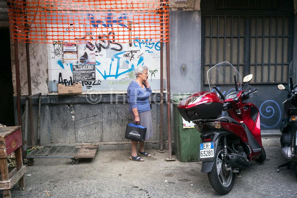 An elderly woman makes a telephone call at the Mercato della Pescheria Market. Catania, Sicily, Italy.