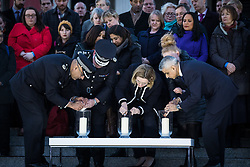 © Licensed to London News Pictures. 23/03/2017. London, UK. Metropolitan Police Deputy Commissioner Craig Mackey (2-L), Home Secretary Amber Rudd (centre) and Mayor of London Sadiq Khan (R) light candles at a vigil in Trafalgar Square for the victims of the Westminster terrorist attack, which took place on 22 March 2017. Photo credit: Rob Pinney/LNP