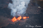 lava emanating from Pu'u O'o on Kilauea Volcano, erupts in three fountains from a fissure in Leilani Estates subdivision, near Pahoa, Puna, Hawaii ( the Big Island ), Hawaiian Islands, U.S.A. ( Central Pacific Ocean ); at upper right frame, the remains of a metal roofed structure are consumed by fire and an asphalt road is covered by lava