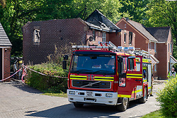 © Licensed to London News Pictures. 06/05/2020. Woolton Hill, UK. A fire engine from the Hampshire Fire and Rescue Service, in the background is the burnt out roof of one of the houses destroyed by fire. A fire has destroyed two houses on Woolton Lodge Gardens, Woolton Hill in Hampshire. The fire started approximately 20:10 BST on Tuesday 05/05/2020. Photo credit: Peter Manning/LNP