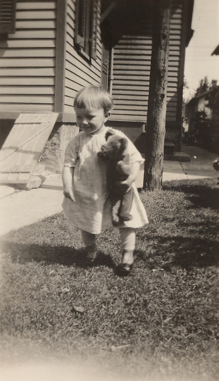 Young boy with stuffed toy, outdoors in front of the house