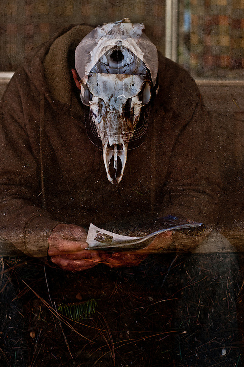 A multiple exposure photograph of a man reading a newspaper with a deer skull.