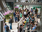 10 MARCH 2016 - BANGKOK, THAILAND: Passengers on C Concourse at Suvarnabhumi Airport in Bangkok.  Suvarnabhumi was officially opened for limited domestic flight service on 15 September 2006, and opened for most domestic and all international commercial flights on 28 September 2006. The airport is currently the main hub for Thai Airways International, Bangkok Airways and Orient Thai Airlines. It also serves as regional gateway and connecting point for various foreign carriers. The airport is located on what had formerly been known as Nong Nguhao (Cobra Swamp) in Racha Thewa in Bang Phli, Samut Prakan, about 25 kilometres (16 mi) east of downtown Bangkok. The name Suvarnabhumi was chosen by King Bhumibol Adulyadej and refers to the golden kingdom, hypothesised to have been located somewhere in Southeast Asia. The building was designed by Helmut Jahn of Murphy / Jahn Architects. It was constructed primarily by ITO JV. The airport has the world's tallest free-standing control tower (132.2 metres or 434 feet), and the world's fourth largest single-building airport terminal (563,000 square metres or 6,060,000 square feet). Suvarnabhumi is the tenth busiest airport in the world, sixth busiest airport in Asia, and the busiest in the country, having handled 53 million passengers in 2012, and is also a major air cargo hub, with a total of 95 airlines. On social networks, Suvarnabhumi is the world's most popular place where Instagram photographs were taken in 2012. The airport inherited the airport code, BKK, from Don Mueang after the older airport ceased international commercial flights.       PHOTO BY JACK KURTZ