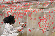 Red hearts that form the National Covid Memorial Wall, a tribute to the 150,000-plus British victims of the Coronavirus pandemic on 1st April 2021, in London, United Kingdom. Bereaved family and friends of Covid-19 victims have started working on the wall located outside St Thomas' Hospital.