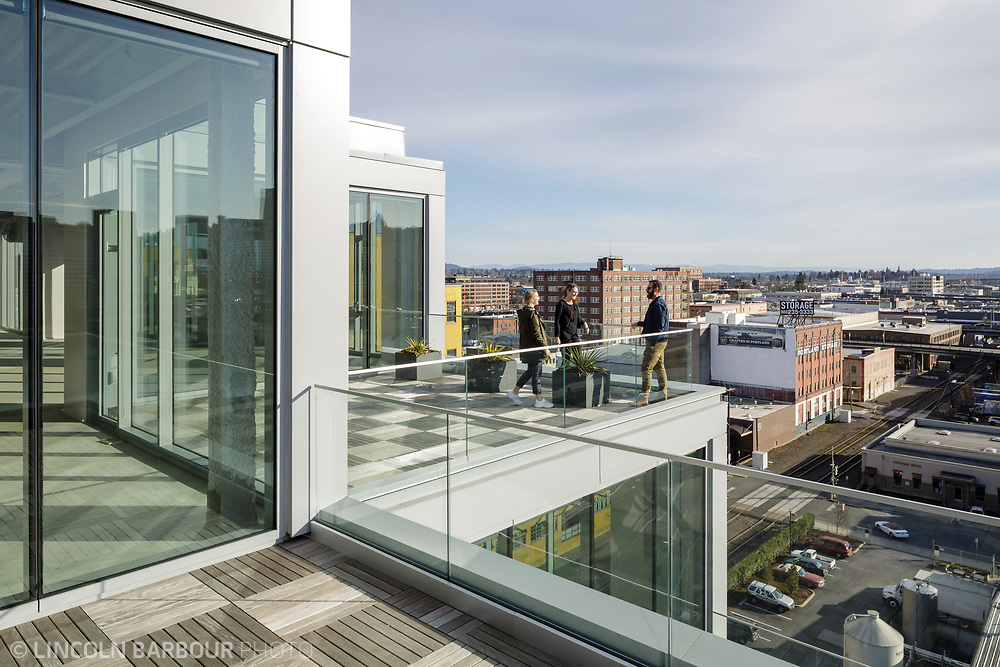 A small group of people converse on one of the terraces of the 7 Stark Building in Portland, Oregon with a view of the east side in the background.