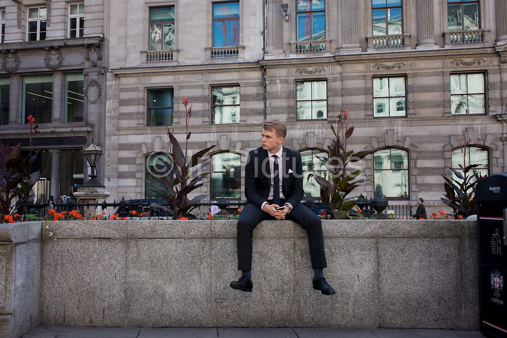 A young City worker waits for a friend on Bank Triangle in the City of London, the capital's financial district and oldest quarter. Sitting on a low decorative flower bed wall in a busy space between many company headquarters and financial and banking institutions, the youth looks successful and confident. He waits patiently for a friend who comes eventually during a lunchtime break from his job here in what is known in London as the Square Mile.