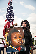 Garrick Rawles  from Hunstsville Alabama   holding  a photo of Micheal Brown and an American flag that is upside down.