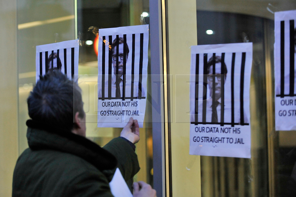 © Licensed to London News Pictures. 20/03/2018. LONDON, UK.  Heiko Khoo, 54, from London, puts up posters outside the building which houses the offices of Cambridge Analytica in central London.  Cambridge Analytica, a UK based data consulting firm, has been accused of using the personal data of 50m Facebook users to influence the 2016 US presidential election.  The UK Information Commissioner is seeking a court warrant to search the premises for evidence of any breaches of the Data Protection Act.  Photo credit: Stephen Chung/LNP