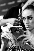 Model reads while her hair is being styled