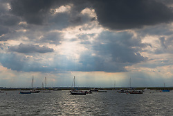Dark clouds slowly drift northwards with the prospect of a spectacular sunset in store at West Mersea, Mersea Island, near Colchester in Essex. West Mersea, Essex, July 10 2019.