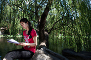 Student studies her report under a weeping willow tree by a picturesque lake on campus at Tsinghua University in Beijing. The school is one of the nine universities of the C9 League. It was established in 1911 under the name 'Tsinghua Xuetang'. The university section was founded in 1925 and the name 'National Tsinghua University' started in 1928. With a motto of Self-Discipline and Social Commitment, Tsinghua University describes itself as being dedicated to academic excellence, the well-being of Chinese society and to global development. Tsinghua is almost always ranked as the first or second best university in mainland China in many national and international rankings. According to the Times Higher Education World University Rankings 2011–2012, Tsinghua ranked 71 worldwide among universities.
