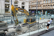 Young boy watches as a workman operating a digger lifts large quantities of rubble into a truck at the construction site for work on the update to the Midland Metro tram public transport system in the city centre along Corporation Street on 3rd August 2021 in Birmingham, United Kingdom. The original tracks are being pulled up and relaid, while a new line is also under construction and due to open later in the year. The Midland Metro is a light-rail tram line in the county of West Midlands, England, operating between the cities of Birmingham and Wolverhampton via the towns of West Bromwich and Wednesbury. The line operates on streets in urban areas, and reopened conventional rail tracks that link the towns and cities. The owners are Transport for West Midlands with operation by National Express Midland Metro, a subsidiary of National Express. TfWM itself will operate the service from October 2018.