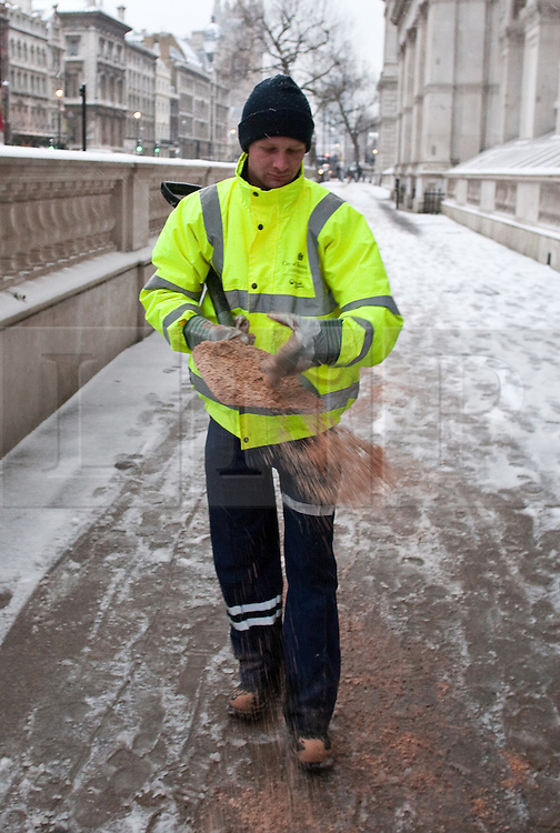 © under license to London News Pictures. 02/12/10. A worker spreads grit to melt snow on Whitehall, London this morning (02/12/2010).  Credit should read Matt Cetti-Roberts/London News Pictures