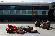 A woman and her husband sleep at the train station in Jaipur.  Children, some who have run away from their families, find themselves living homeless on the train tracks waititng for the next train to arrive at the train station in Jaipur, India.  Once the train arrives they raid the train looking for plastic bottles that they can then sell.  Most will make about $1.50/day but spend most of it on glue which they are most addicted to.