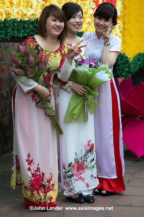 The ao dai is now most commonly worn by women. In its current form, it is a tight fitting silk tunic worn over pants. The word ao dai was originally worn at the court of the Nguyen Dynasty at Hue in the 18th century. This outfit evolved into a modern dress in the 1920s and 1930s.   This updated look was promoted by artists and magazines as a national costume for the modern era. In the fifties, Saigon designers tightened the tunic part to produce the version worn by Vietnamese women today.  On Tet and other Vietnamese holidays and occasions, Vietnamese men may wear an ao gam brocade robe, a mens version of the ao dai, made with less bright colors.
