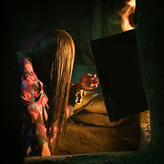This woman  just married. Here she dries her hair in front of the open fire. That's in a home where I stayed 12 years ago. House of Kush Namaz and Darvish. The life of the Wakhi people, in the Wakhan corridor, amongst the Pamir mountains. Trekking with Paul Salopek.