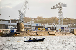 """Embargoed to 0001 Thursday June 15 File photo dated 04/12/15 of police patrolling around HMS Vanguard, one of the UK's nuclear deterrent V-Class submarines. Plans for further cuts to the Ministry of Defence Police (MDP), the police force that guards Britain's nuclear arsenal could be """"catastrophic"""", a leading officer will warn."""