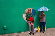 As rain starts falling, a chinese husband and wife wait for a bus on Nathan Road in Hong Kong's Tsim Sha Tsui