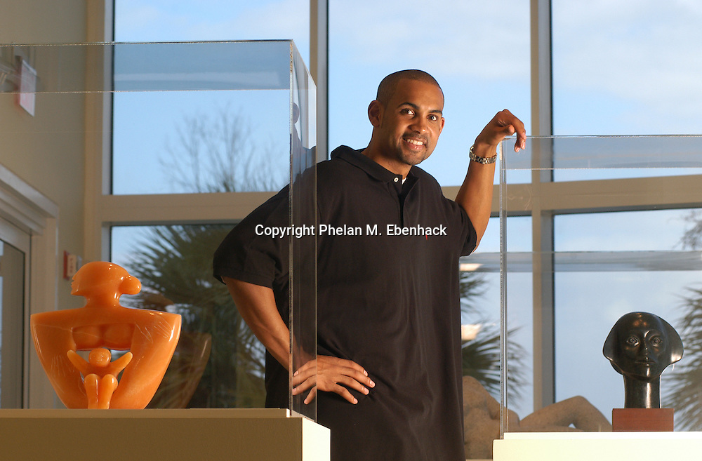 National Basketball Association player Grant Hill stands with some of his collection of African-American artwork on display at the Orlando Museum of Art in Orlando, Florida.