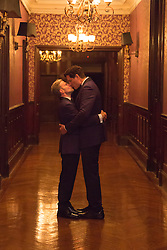 gay couple embracing and kissing on their wedding day