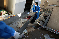 Workers are seen organizing the dead for identification at Al Karah hospital in Baghdad, Iraq, Feb. 11, 2004. A suicide attacker detonated a car packed with explosives in a crowd of hundreds of Iraqis waiting outside a Baghdad army recruiting center Wednesday, killing up to 46 people in the second bombing in two days targeting Iraqis working with the U.S.-led coalition. The attack backed threats that insurgents would step up violence to disrupt the planned June 30 handover of power to the Iraqis.