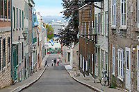 The narrow streets of Old Quebec City are lined with tall European apartments and lead down to the water. The Holland America boat Queen Mary waits in the cruise ship terminal below.