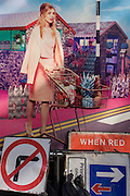 Roadworks signs below a fashion poster featuring a young woman about to cross a road in a utopian fantasy.