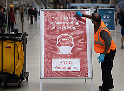 © Licensed to London News Pictures. 07/09/2020. London, UK. A worker cleans a sign at Waterloo Station warning passengers of a £100 fine for not wearing a face covering. Train capacity is supposed to reach 90% today as holidays come to an end and schools return. Photo credit: Peter Macdiarmid/LNP