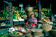 Woman stallholder holding the knife she uses to cut fruit for sale in the market in Kathmandu, Nepal.  Her stall displays in baskets fruit, vegetables and dried fish.