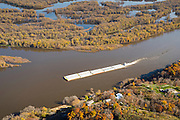 A barge plies the waters of the Mississippi River on a beautiful autumn day.