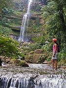 A hiker crosses a stream near a waerfall in San Gil - Colombia