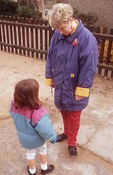 Nursery school teacher talking to child in playground,