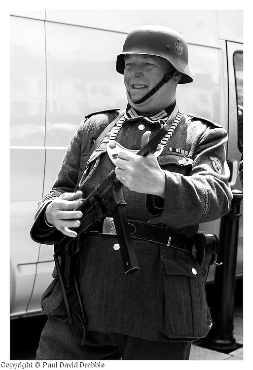 Air Guitar no its air ukulele in Northallerton town square as a Feldgendarme joins in using his MP40 as an instrument joins in with Geroge Formby. Certainly not a face of the Feldgendarmerie the German Soldiers of the second world war would have been used to seeing. <br /> <br /> 15 June 2013<br /> Image © Paul David Drabble<br /> www.pauldaviddrabble.co.uk