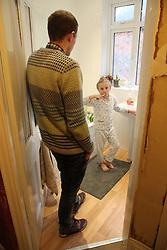 Father watching daughter brushing teeth