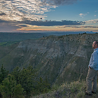 A hiker stands above eroded coulees drain into the Judith River Valley in the Upper Missouri River Breaks of central Montana.