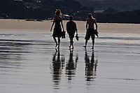 Friends strolling on the beach at Gwithian in Cornwall